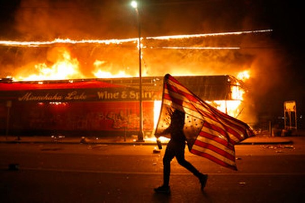 Minneapolis protester carries the carries a US flag upside down, a sign of distress, Thursday, May 28, 2020. (AP Photo/Julio Cortez.)