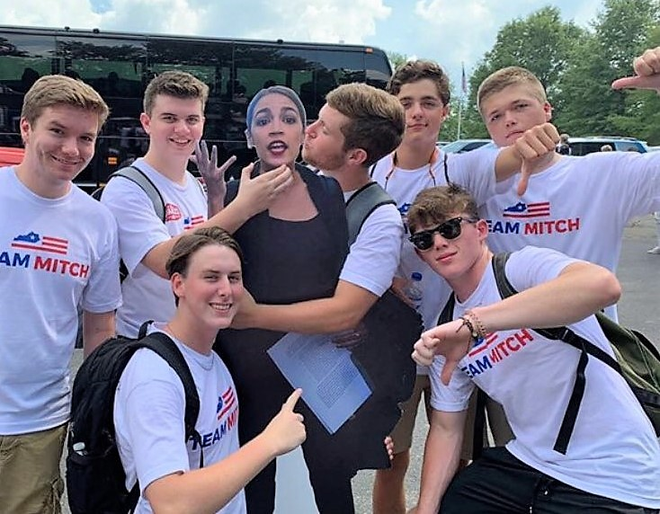 AOC Rips McConnell Over Pic Of Men In 'Team Mitch' Shirts 'Groping & Choking' Cutout Of Her
