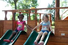 2-Kindergarten-Students-Holding-Hands-on-Slide-Near-Burlington-and-Greensboro-NC