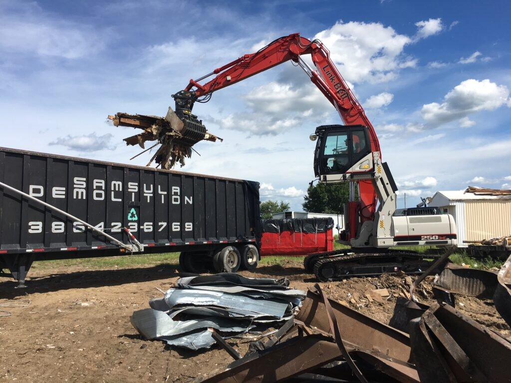 Excavator loading metal onto a truck on a demolition job.