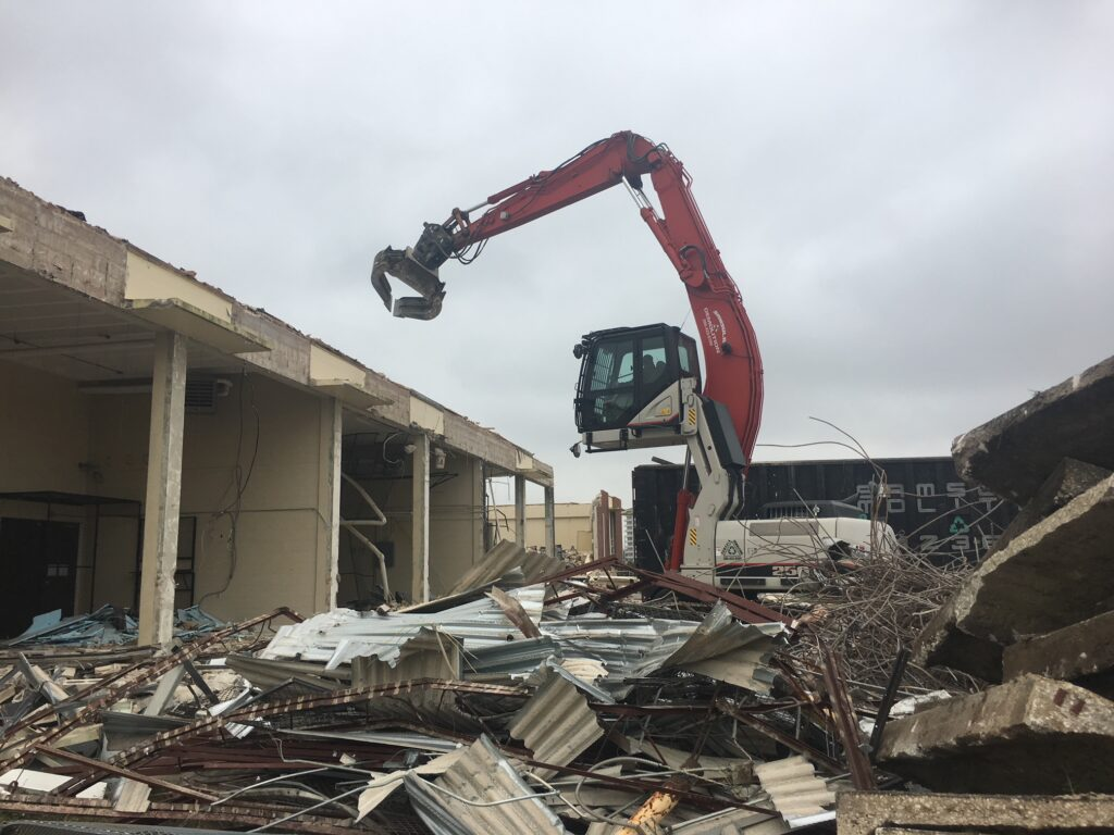 Excavator conduction a demolition of a concrete building to recycle it.