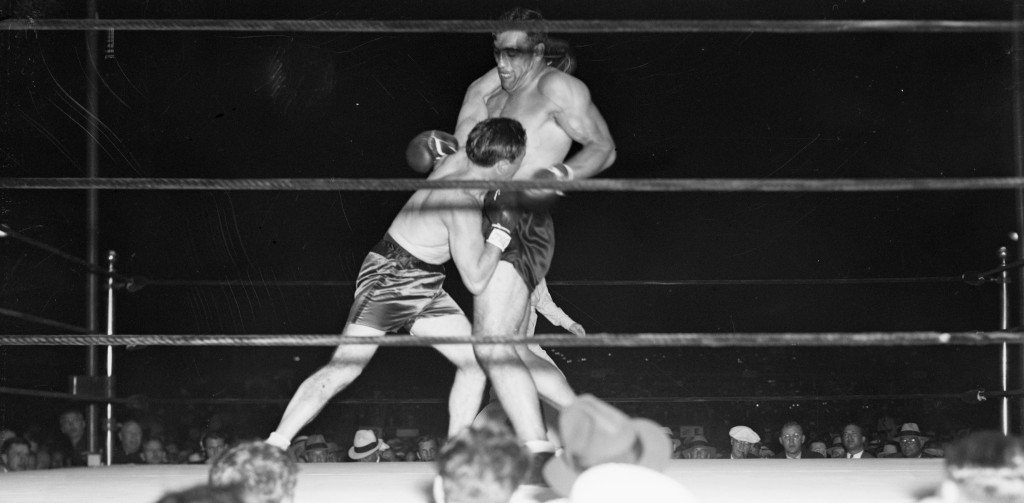 01 Mar 1934, Miami, Florida, USA --- 3/1/1934-Miami, FL- Using his greater height and weight to advantage, Primo Carnera successfully defended his heavyweight championship against Tommy Loughran when he was awarded the decision at the end of 15 rounds. With Carnera towering over him, Loughran is shown here missing a left lead to the champion's head. --- Image by © Bettmann/CORBIS