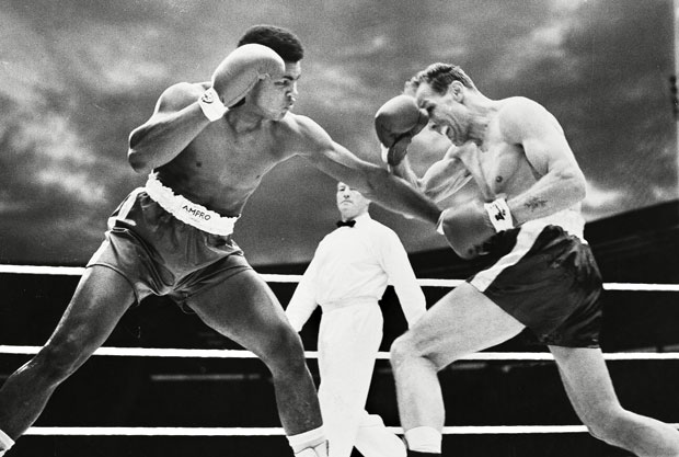 Cassius Clay and Henry Cooper slug away in their first meeting.