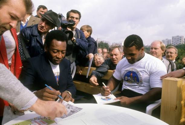 Mike Tyson and Pele signing autographs