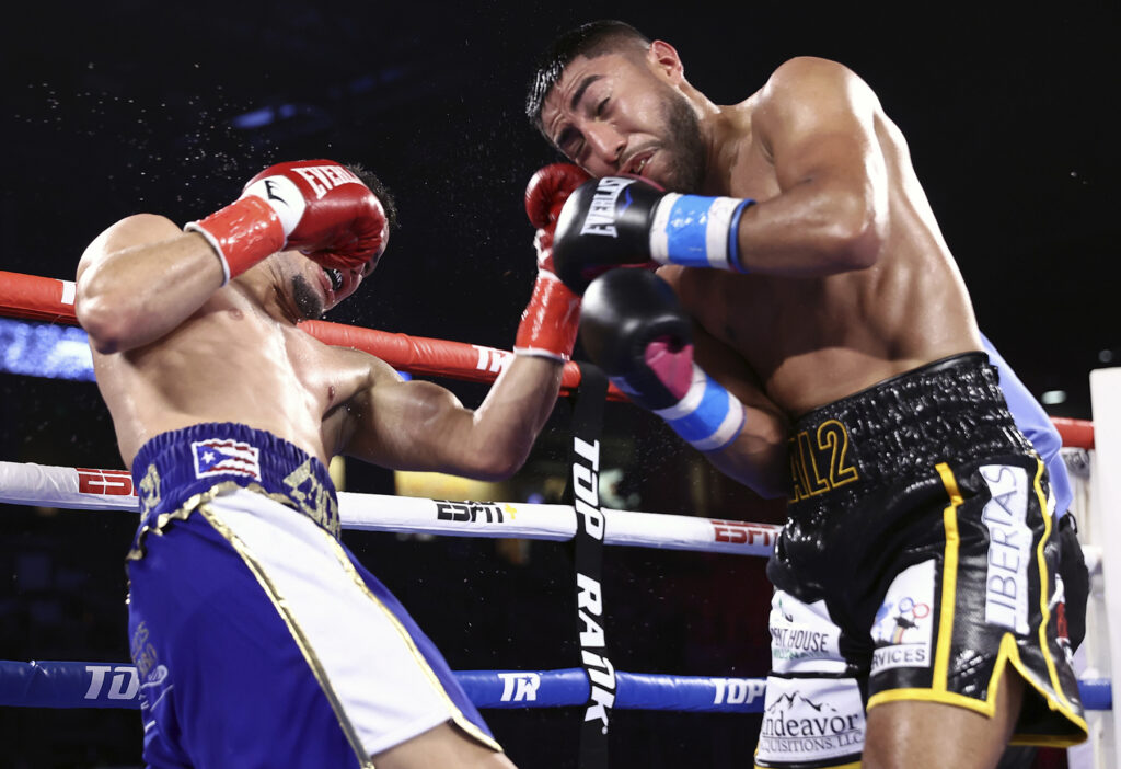 Orlando Gonzalez (L) lands a left hook to the jaw of Juan Antonio Lopez (R).