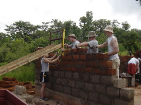 Joe with his students building a medical clinic in Lusyomo, Zambia.