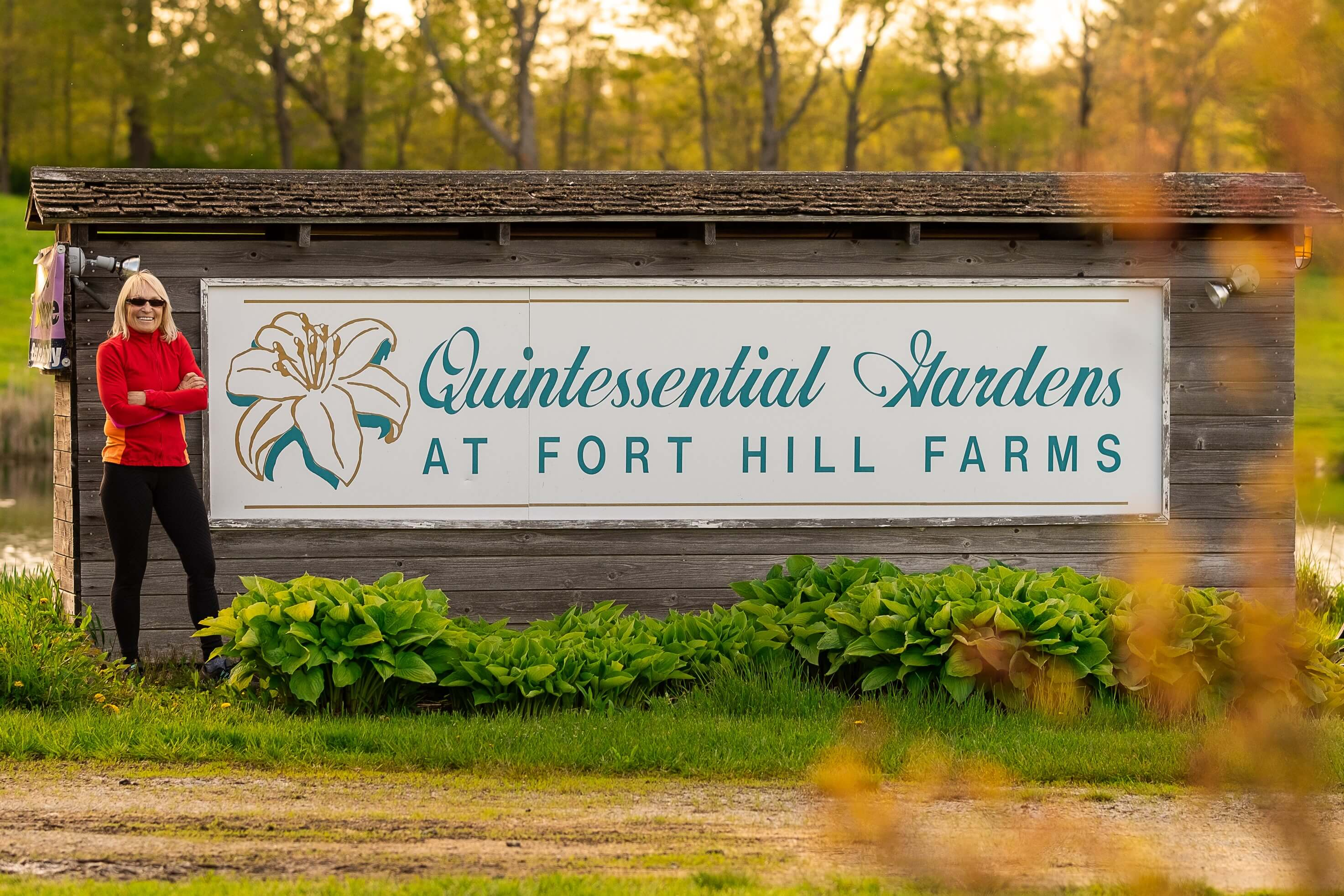Kristin Orr by the Quintessential Gardens at Fort Hill Farms sign