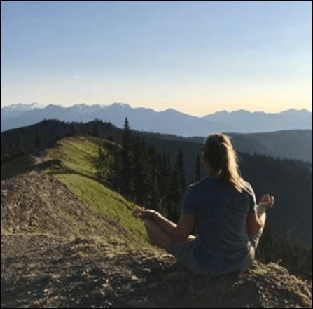 Woman on top of mountain meditating
