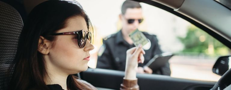 woman handing over license to police criminal law fargo