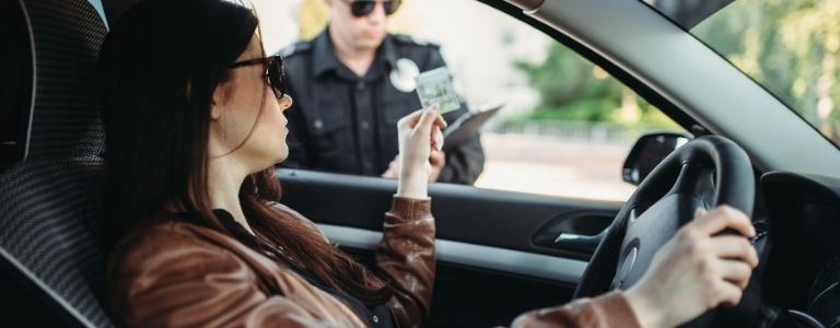 woman handing drivers license to cop criminal law fargo