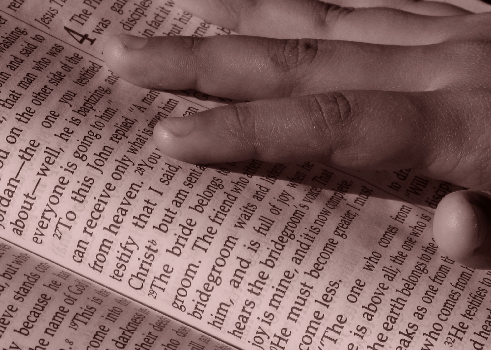 photo of hand resting upon opened Bible