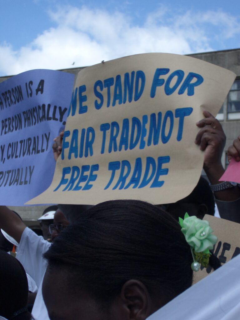 """A photo of a demonstration with a sign that reads, """"We stand for fair trade, not free trade."""""""