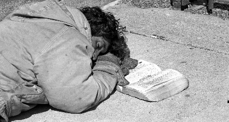 Photo of sleeping homeless man with open Bible