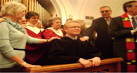 Photo of the laying on of hands at the ordination service
