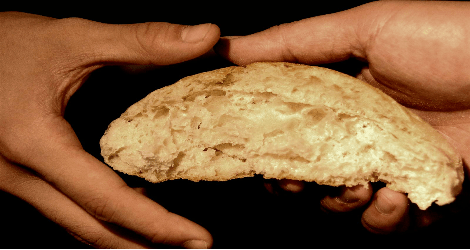 photo of two hands sharing bread