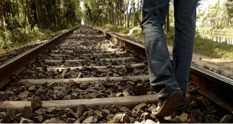 photo of person walking along railroad tracks