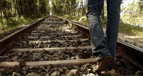 photo of person walking along railroad tracks