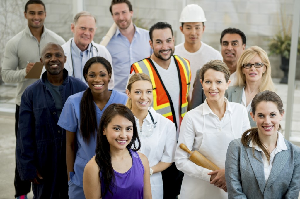 A multi-ethnic group of mixed professionals standing together in their work attire.