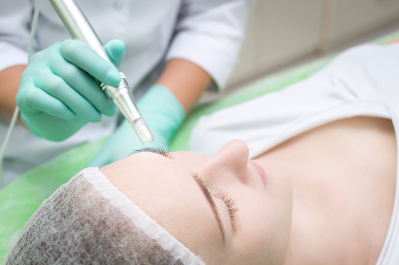 Beautician makes microneedling young girl in the beauty salon close-up mezo roller