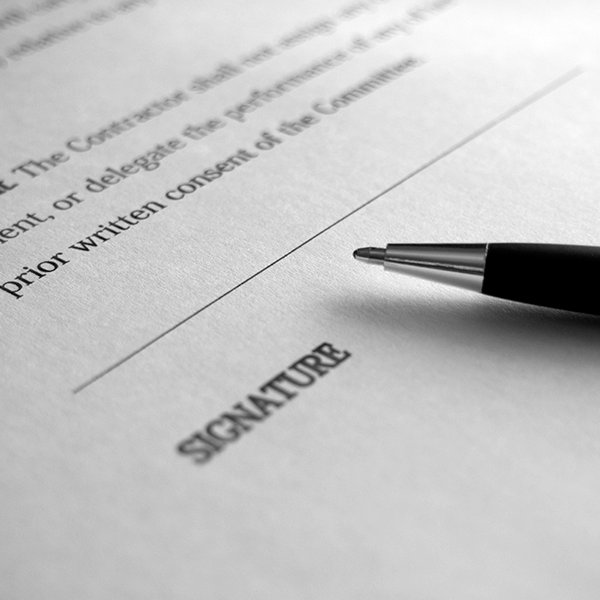 Ballpoint pen laying on a contract next to the signature line.