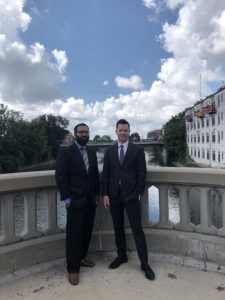Two men in suits standing next to each other with a building and river behind them.