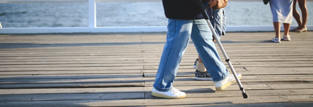 A close up image of a person walking on a boardwalk using a cane as a mobility aid