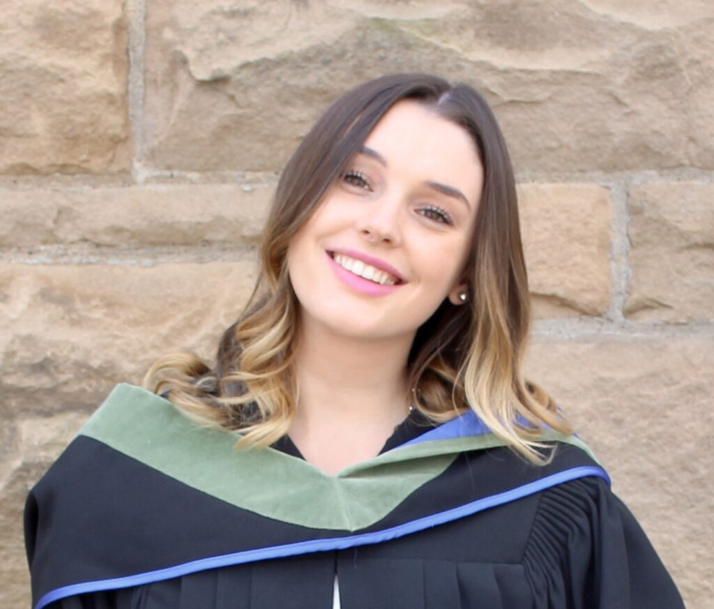 A smiling woman in a graduation gown