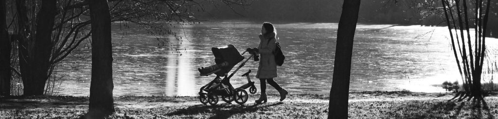 A woman pushes an enfant in a baby carriage along a pedestrian path