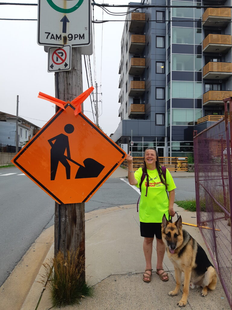 A woman stands on a sidewalk giving the finger to a diamond shaped construction sign strapped to a telephone pole at head level, with her guide dog sitting next to her.