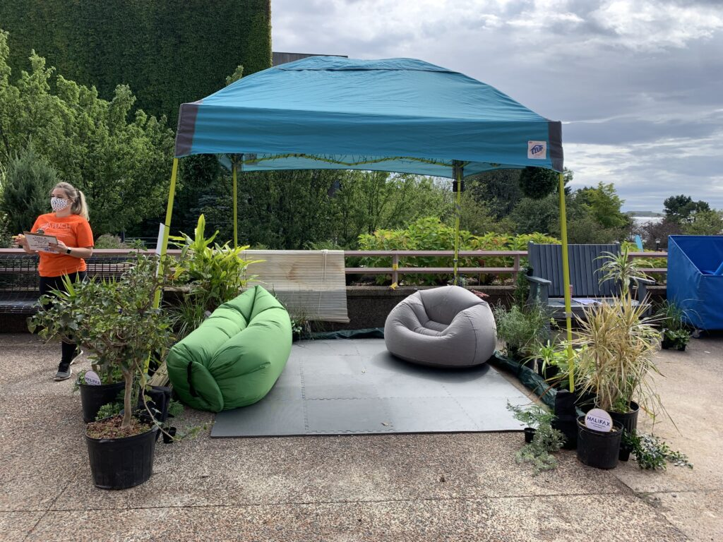 A temporary blue tent canopy is set up with inflatable seating and soft tile flooring underneath, surrounded by potted plants.