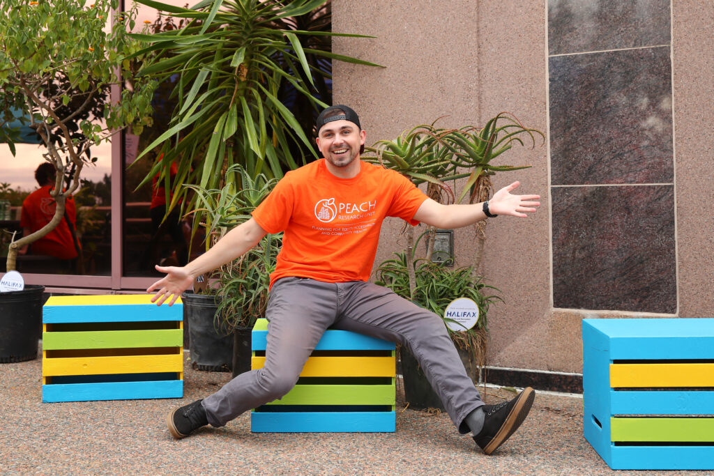 A young man wearing an orange PEACH Research T-shirt smiles and poses with his arms wide to show off colourful crate seats built for the event