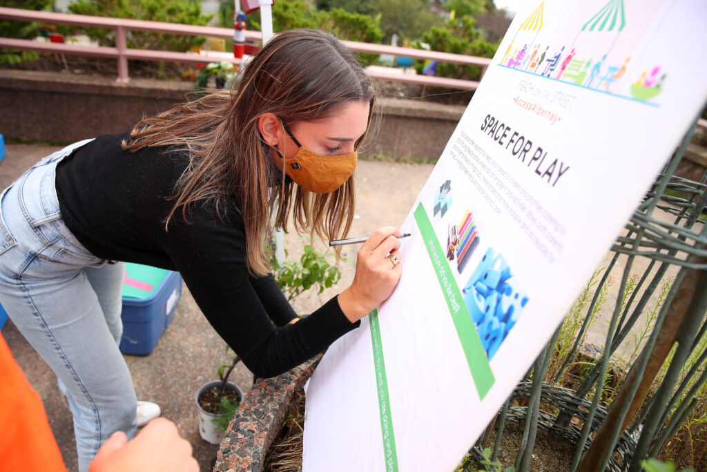 A young woman leans over to write on a poster board asking for community feedback on public play spaces
