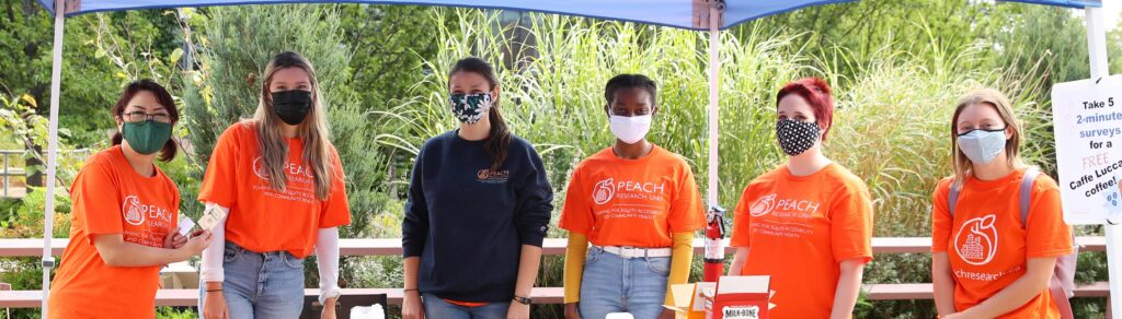 Six people wearing PEACH shirts and face masks stand in a row and smile.