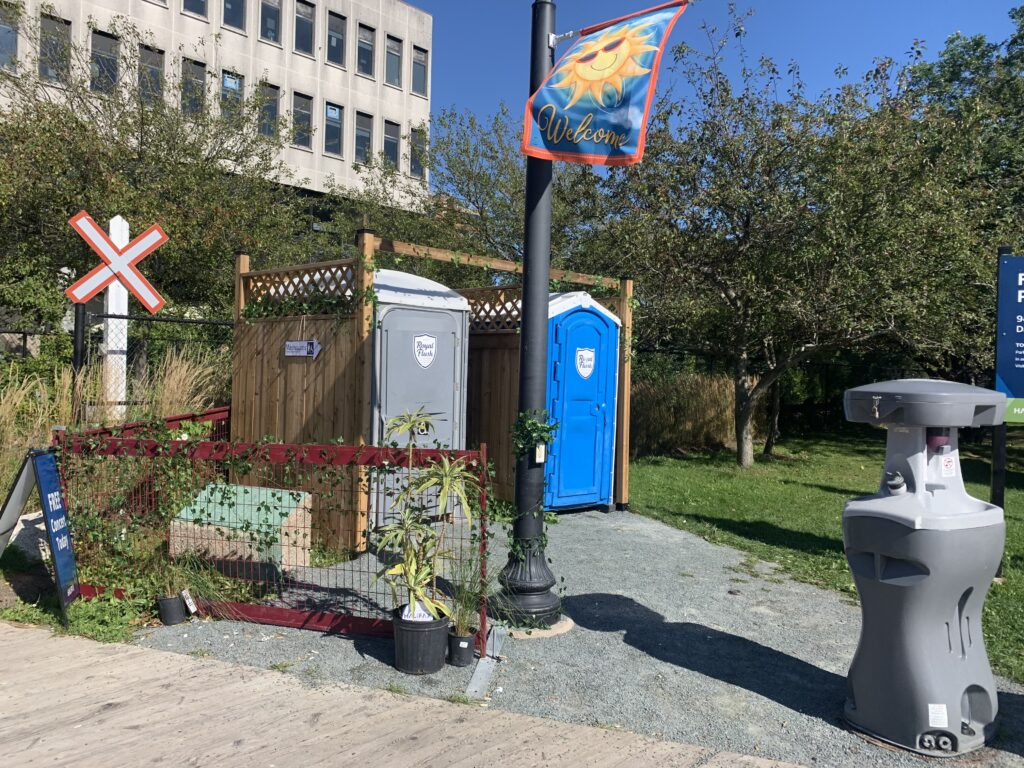 Two portable washrooms are enclosed by a wooden structure with vines wrapped all around it and potted plants placed at the entrance.