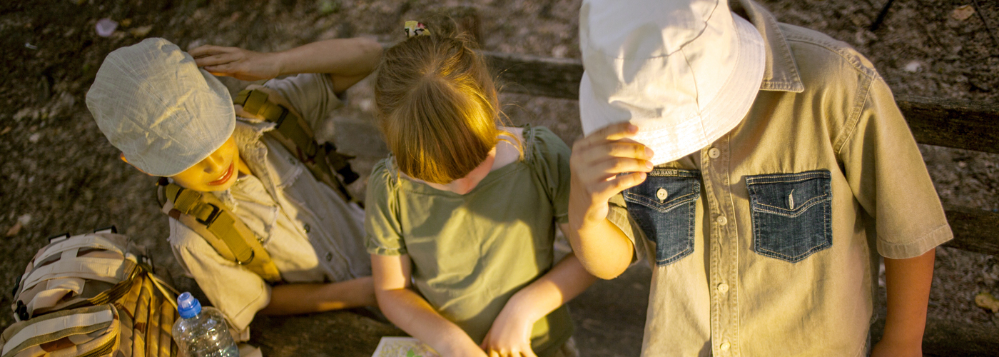 Little boys and girl go hiking with backpacks on a forest