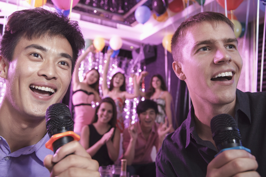 Two friends holding microphones and singing together at karaoke, friends in the background