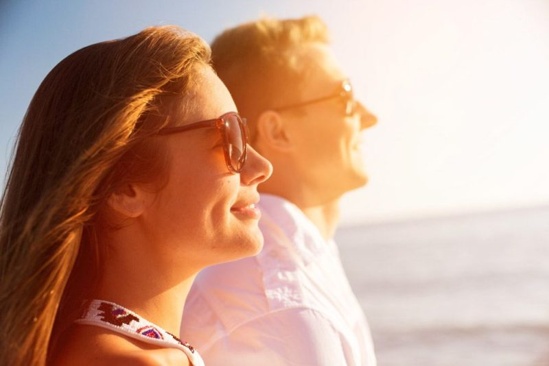 Young couple wearing sunglasses and looking out to sea.