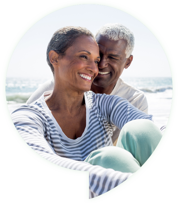 man and woman smiling while sitting on a beach
