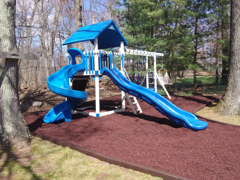 backyard playset with red mulch