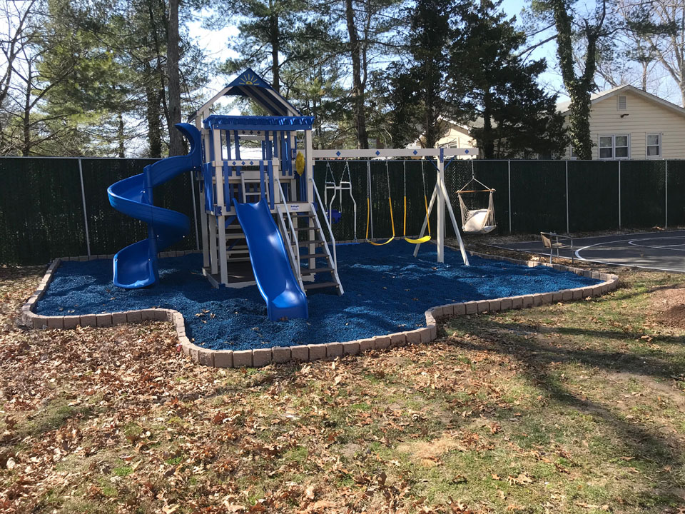 outside playset with blue mulch