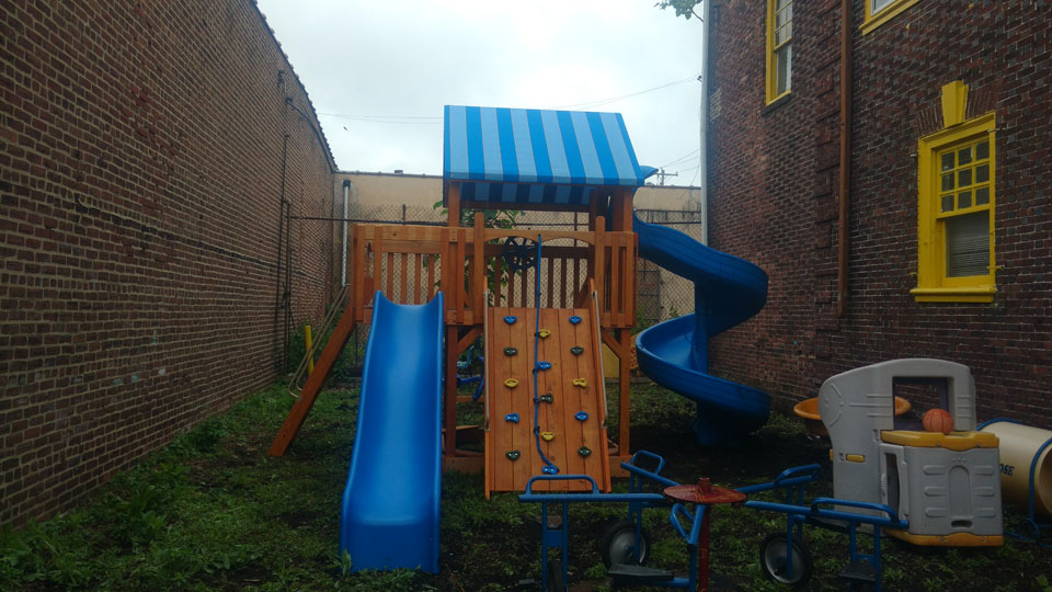 playset with slides and a climbing wall