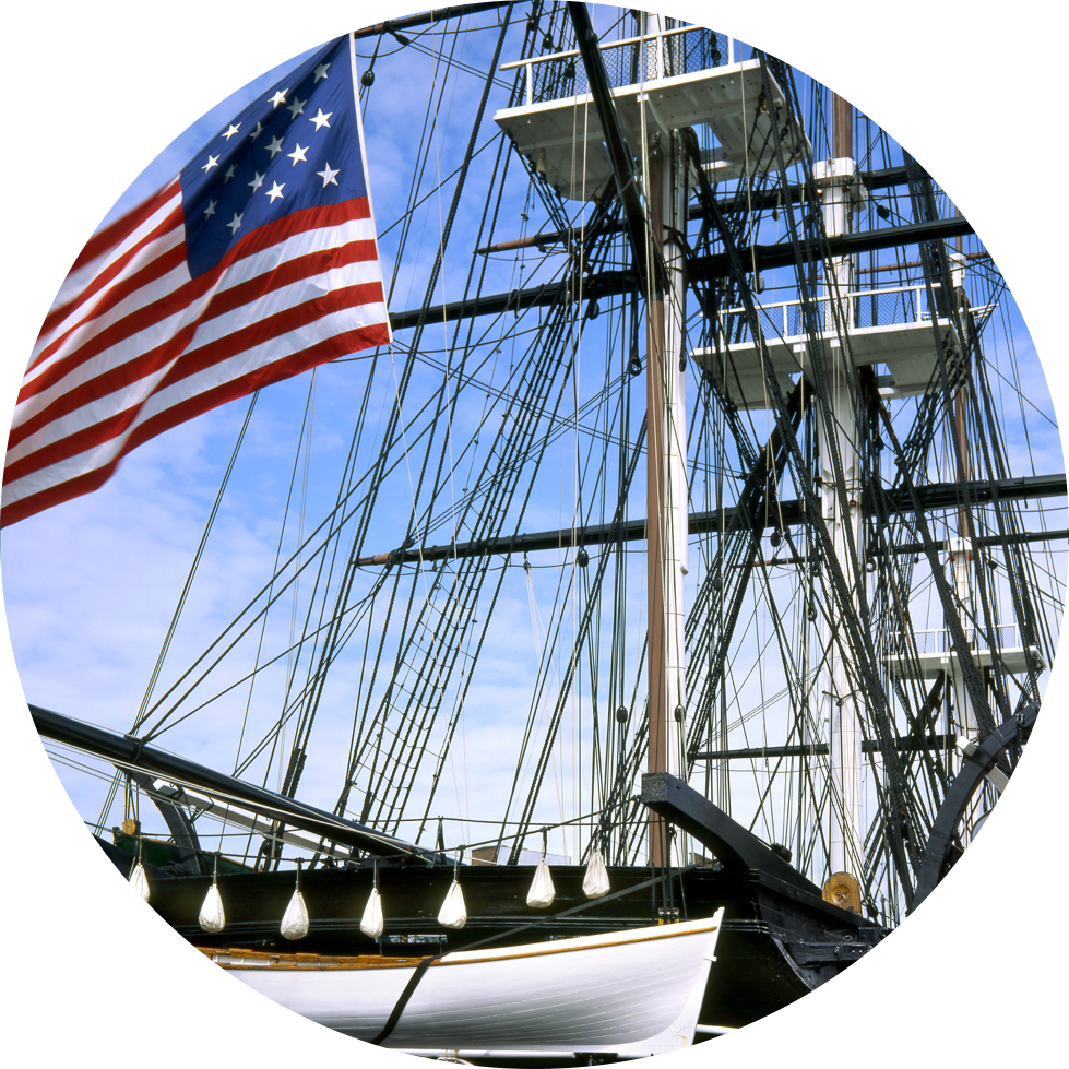 Image of USS Constitution's masts and large USA flag flying