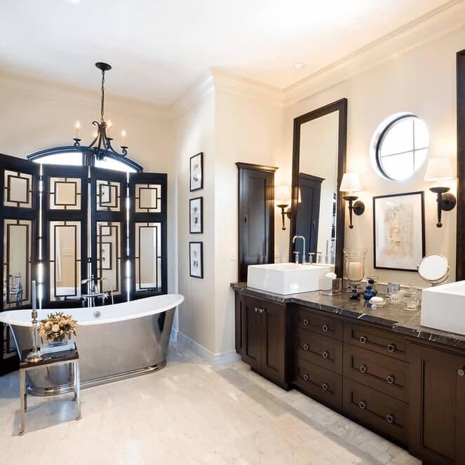 Elegant bathroom featuring marble tiled floor, large mirrors and a standalone metal bathtub.
