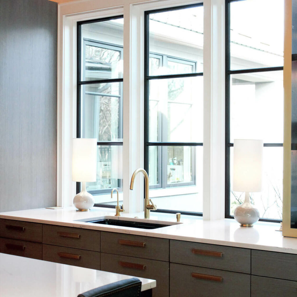 White marble counter top with windows behind a sink with gold fixtures.