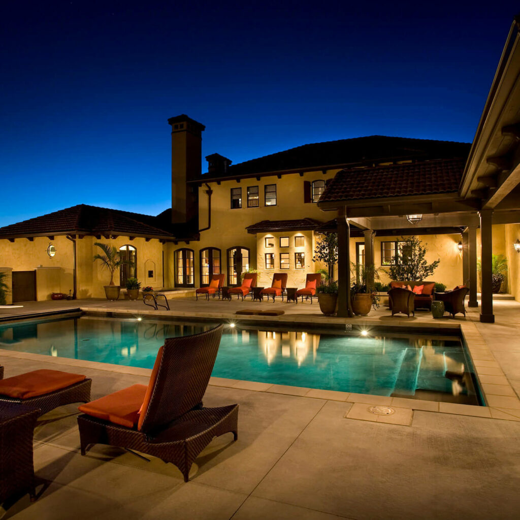 Illuminated courtyard at night with pool behind a large Mediterranean-style home, including orange patio furniture