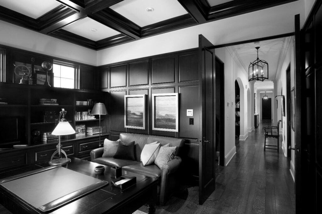 Black and white image of an office with leather furniture and wood decorated walls.