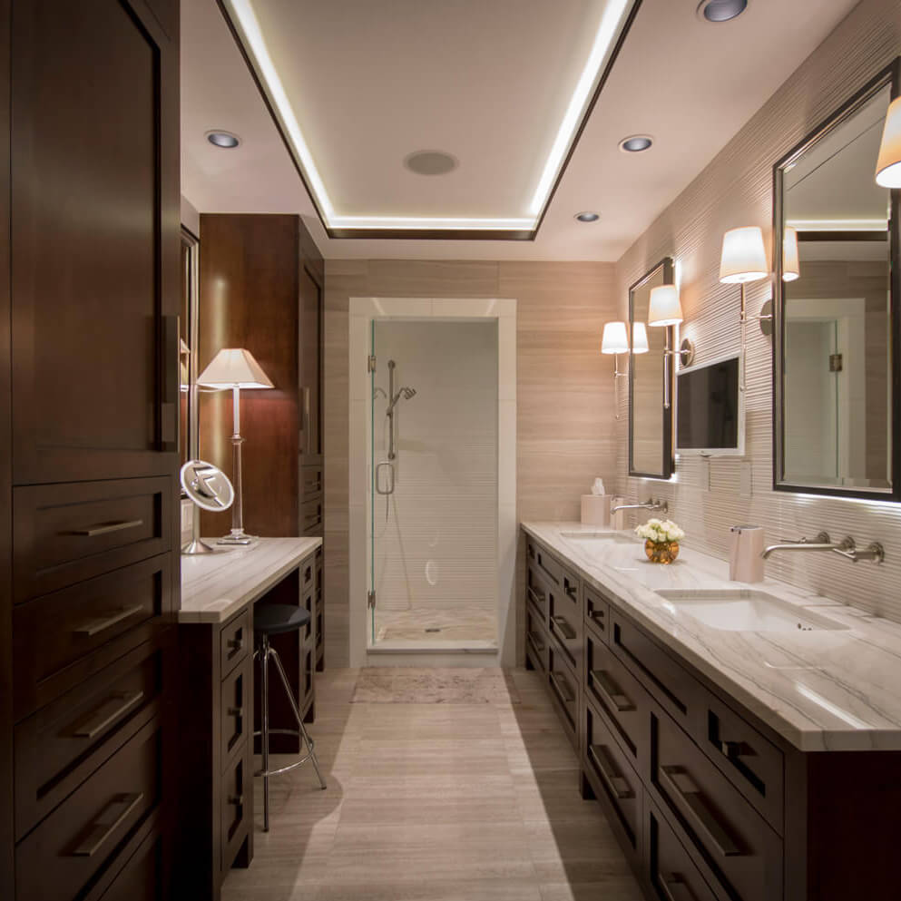 Long bathroom with dual sinks and recessed lighting on the ceiling, featuring striped white marble countertops and dark wood cabinets.