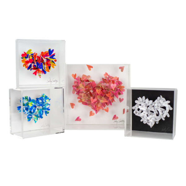 Four acrylic boxes showcasing paper hearts pinned to white and black backgrounds.