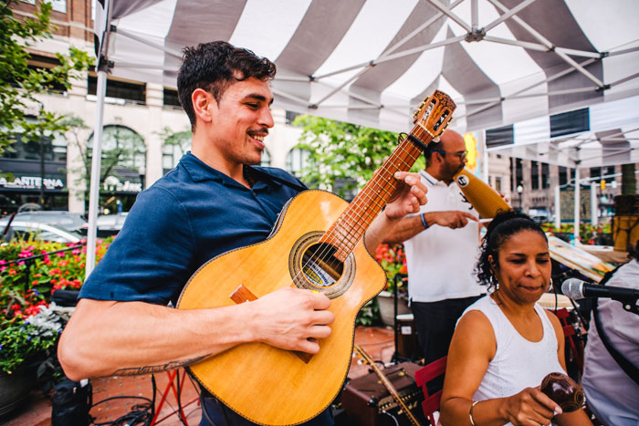 small mariachi band playing guitar and music in downtown detroit