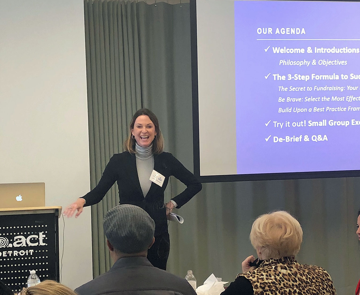 image of Aly Sterling standing infront of a presentation screen, teaching the CultureSource members in a workshop setting